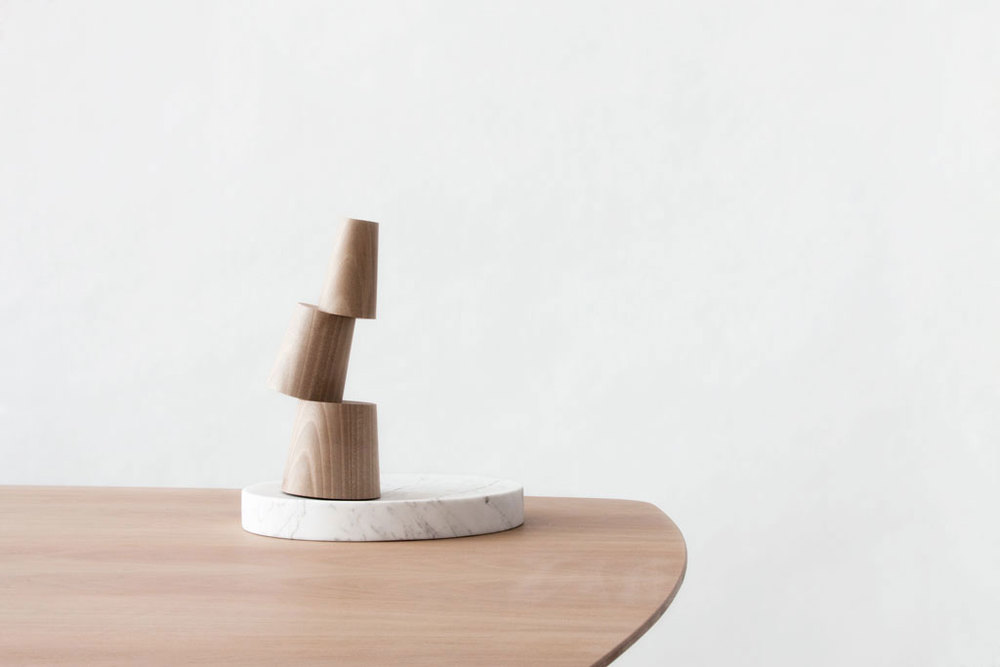 Totem mortar on top of a table. Object handcrafted on marble and wood. Photo by Sergi Vich