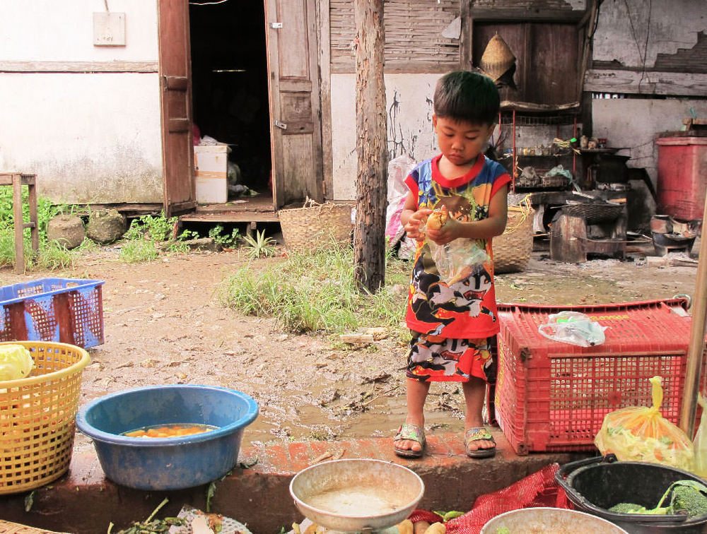 Child preparing food in a #laos market/ sergivich.com