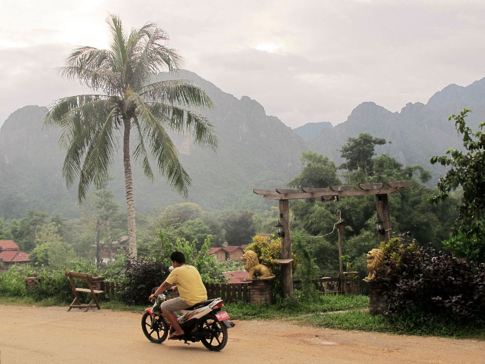 Moto driver passing in front of a temple #laos / sergivich.com