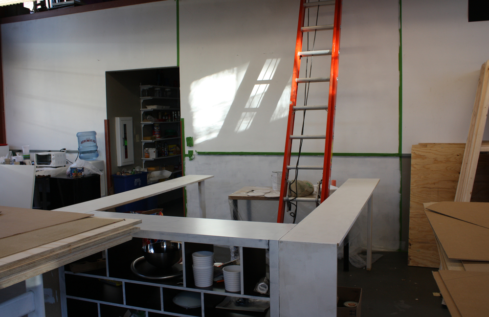 I roughed out the space using a combination of 2x4s, chipboard and IKEA furniture, then primed the space to be painted. I felt it was important to paint the walls something other than institutional white and beige in order to make it an authentic shop experience.