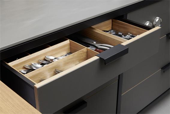 Funktional edel: Die Schubladen mit höchstem Ausziehkomfort sind an rund gefalzten Griffen handfest zu öffnen. Der Besteckkasten aus Eiche bringt Ordnung in die Schublade.