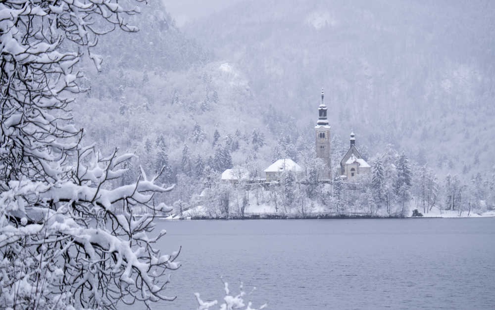 General view on Lake Bled in Slovenia with its Castle and church during a snow storm