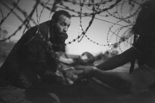 Hope for a New Life                                               Spot News, first prize singles August 28, 2015    A man passes a baby through the fence at the Hungarian-Serbian border in Röszke, Hungary, 28 August 2015.