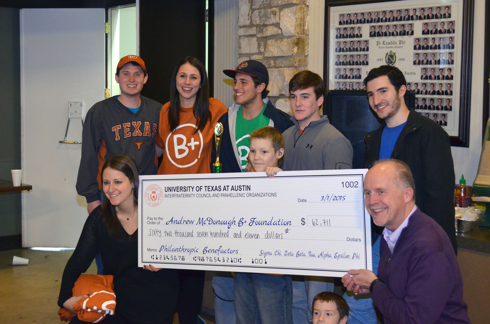 Annotator Max Green, Alpha Nu 2016, and Evan Amann, Alpha nu 2016, pictured among those representing the Ut greek organizations presenting funds to the B+ Foundation
