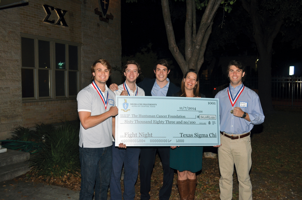 Parker Montieth, Alpha Nu 2015, Andrew Bain, Alpha Nu 2016, Derrick Porter, Alpha Nu 2016, and Andrew Kuchta, Alpha Nu 2015, present a check to Lori Kun of the Huntsman Cancer Institute for $60,000 for funds raised from fall 2014's Fight Night.