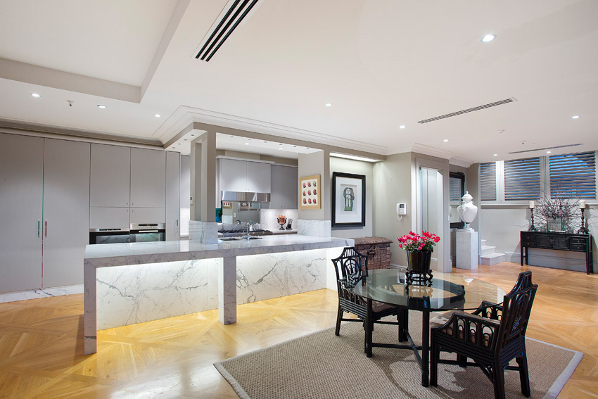 An ultra modern kitchen is situated in an open planned living area.