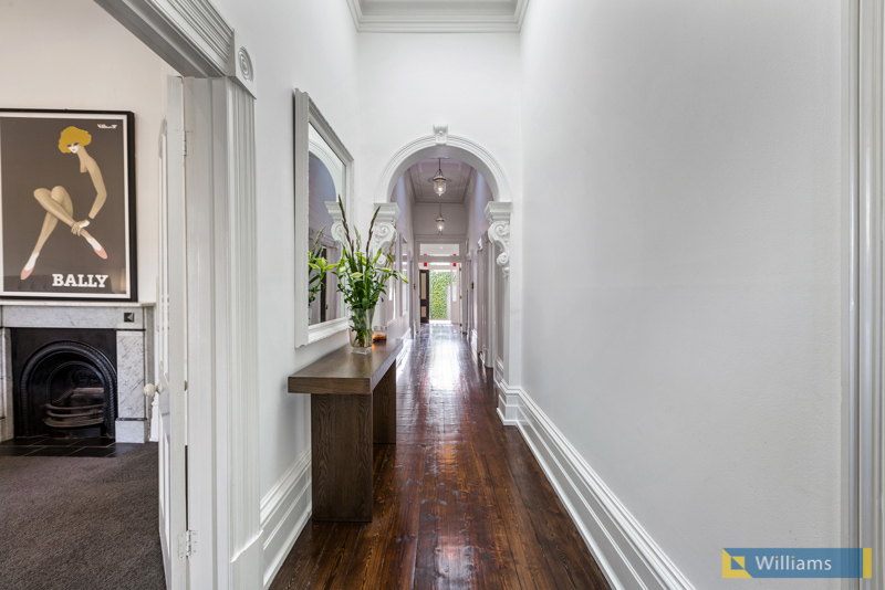 Long corridors with beautiful wooden flooring are an amazing feature of this home.