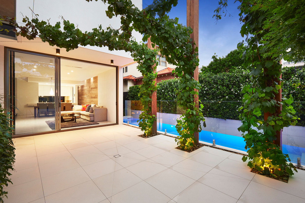 The greenery is prominent outside, beside the slim pool.