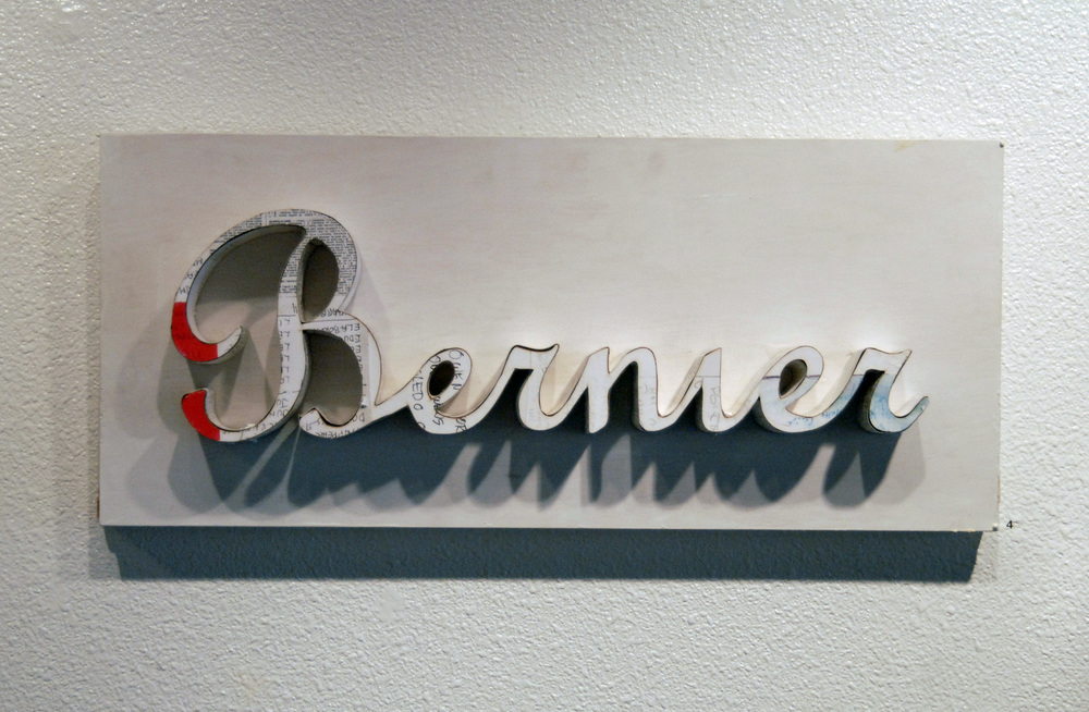 "Bernier Signature in Red, White, and Black  Wood and xeroxed paper  12"" x 27"""