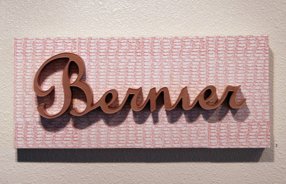 "Bernier Plaque, 2013  Wood, xeroxed paper  27"" x 12"""