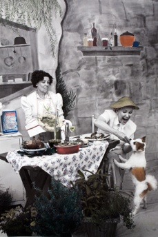 "An Exceptional Lunch Served by Madame E. Saint-Ange to M.F.K. Fisher and a Surprise Guest, Pom-Pom, Somewhere in Northern France, 1949  Archival carbon pigment print  27"" x 40"""