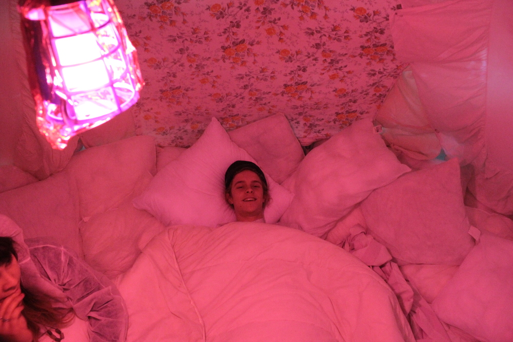 SoftSpot, 2013  Electrical conduit frame, pillows, bedding, safety pins, gaffa tape, cotton,pink cellophane and light  3000mm x 3000mm x 2500mm  Photo: Brenton Alexander Smith