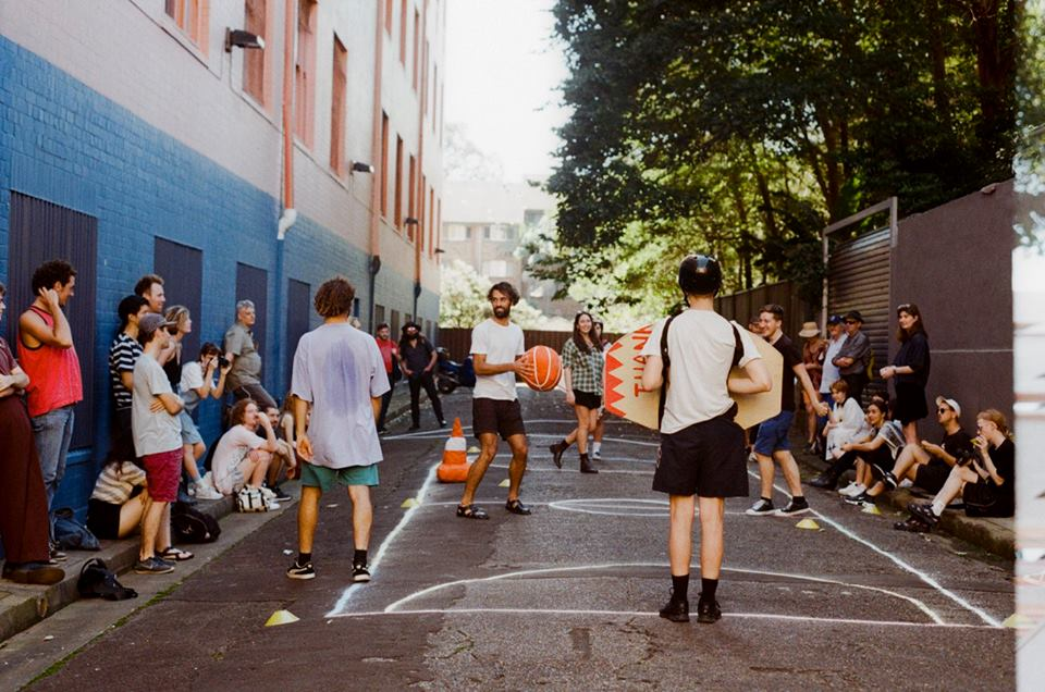 Alley Jam, 2017  Collaborative performance with the help of Luke O'Donnell, Julien Bowman, Allison Chiew (mum), Celeste Stein, Georgia Goldsworth, Emerald Dunfrost and audience members.   Chalk, Plywood, cotton, plastic cones, bike helmets, string, acrylic paint, sports lux, oranges in tupperware, Music: 'Let's get ready to rumble' Space Jam, 1996  Desire Lines 3.0 (Ultimo Edition)  Photo: Valentina Penkova