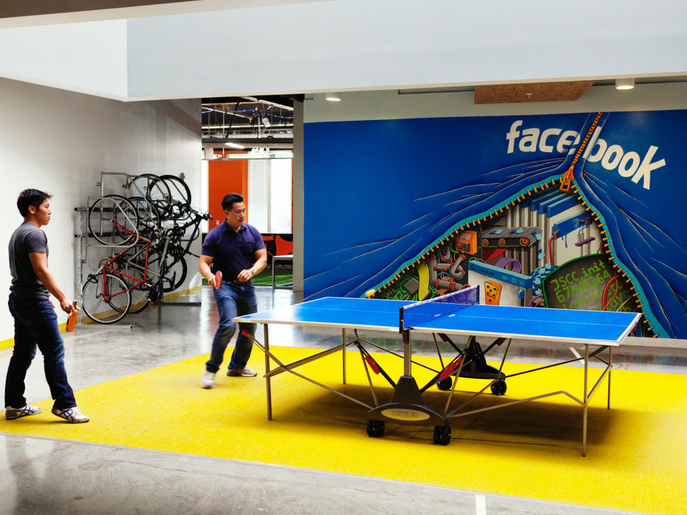 Facebook employees play ping pong near a mural by Shaun Logan, Menlo Park, Calif., Nov. 11, 2014.