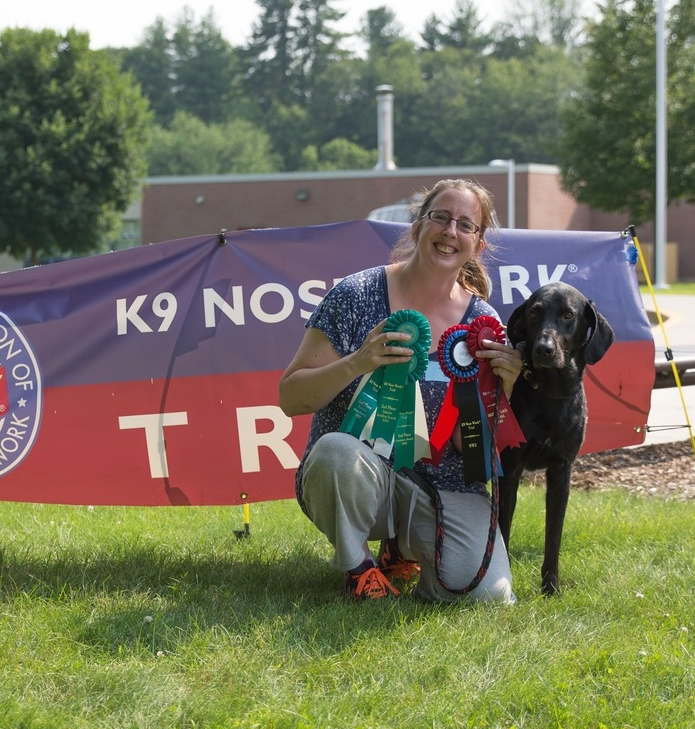 Stacy with Judd, showing off their many Nosework awards. Good job Judd and Stacy!