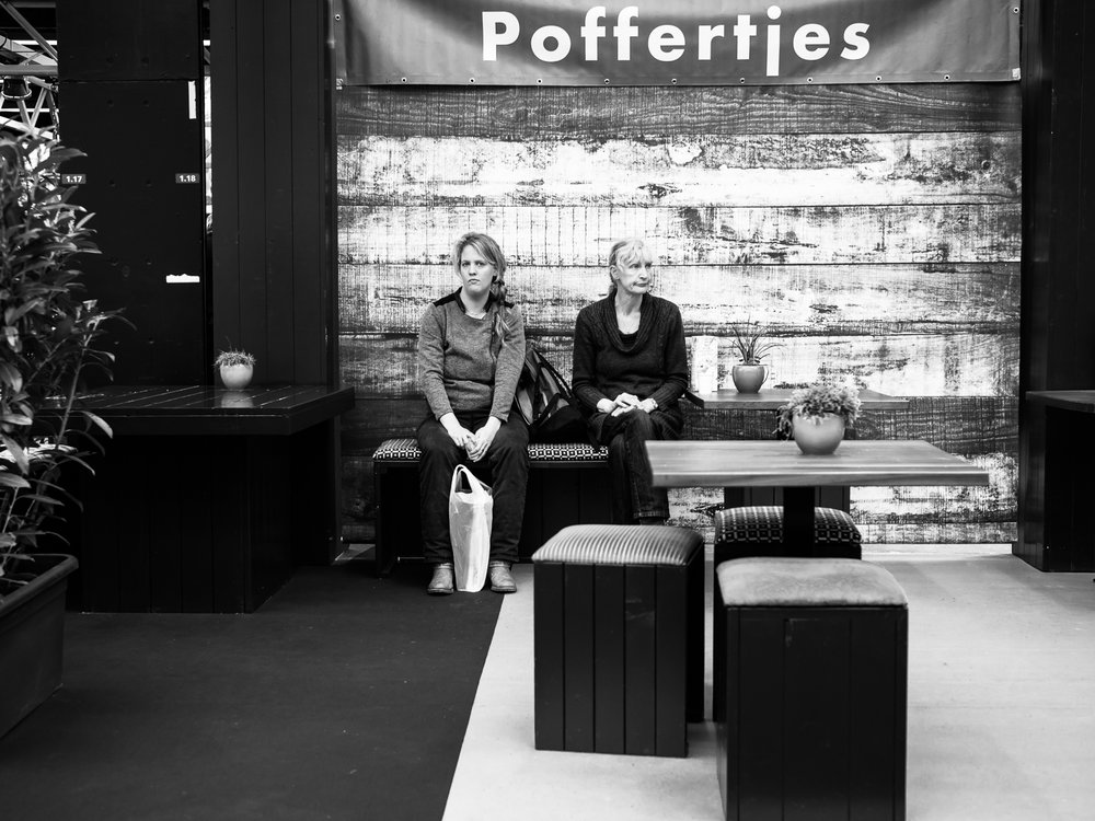 "Shot taken in Amsterdam.  The ""Huishoudbeurs"" (Housekeeping Fair) in Amsterdam is a place where 95% of the visitor are female. You can find all kinds of products and services that you can use in the household. It's fun for street photographers too to visit these kind of events. You can see female friends and also mothers with daughters. As you can see it can be quite boring or tiring. Click    here    to see a selection of my visit in 2016.  Shot with Olympus OMD1 Mark 2 and Olympus 25mm f/1.2"