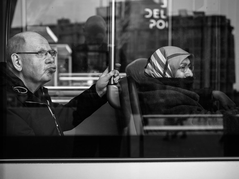 Shot taken during my workshop street photography in Rotterdam. Endless possibilities to make photos of people behind glass in trams, trains, buses and restaurants. Be aware of your own reflection when you shoot at 90 degrees. It's safer to choose a slightly different angle, preferable to show the face of your main character.  Shot with Olympus OMD1 Mark 2 and Olympus 25mm f/1.2