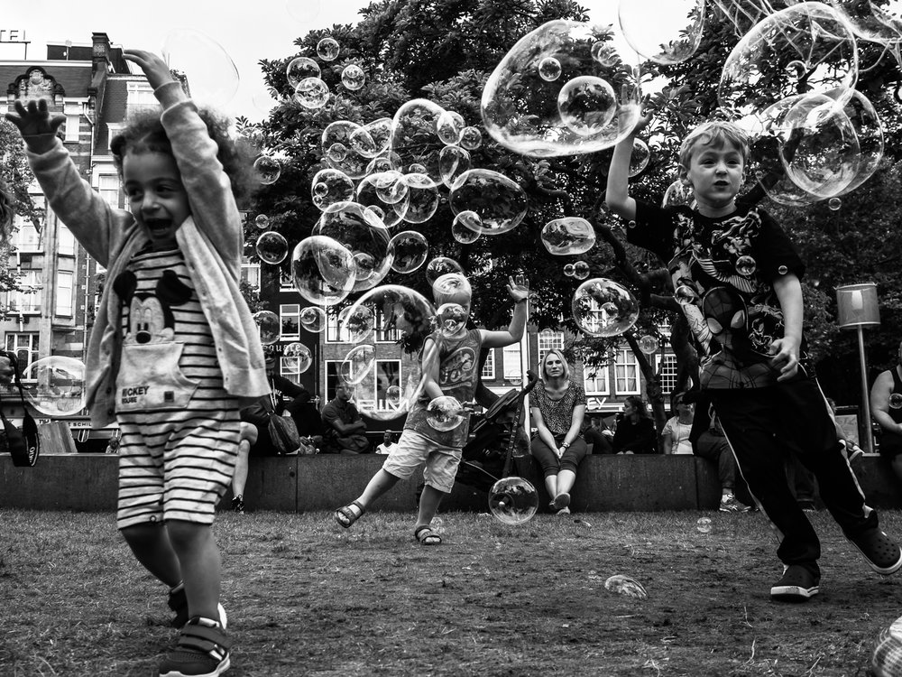 Photo taken in Amsterdam Rembrandplein in July 2017. I had a meeting with other street photographers, all part of the Facebook group Streeteyes. It was fun talking and walking with other passionate photographers. Not easy to shoot bubbles as they moved fast in the wind or were destroyed by the kids. I very much like the expressions and balance in this photo.  Shot with Olympus OMD1 Mark 2 and Olympus 17mm f/1.8.
