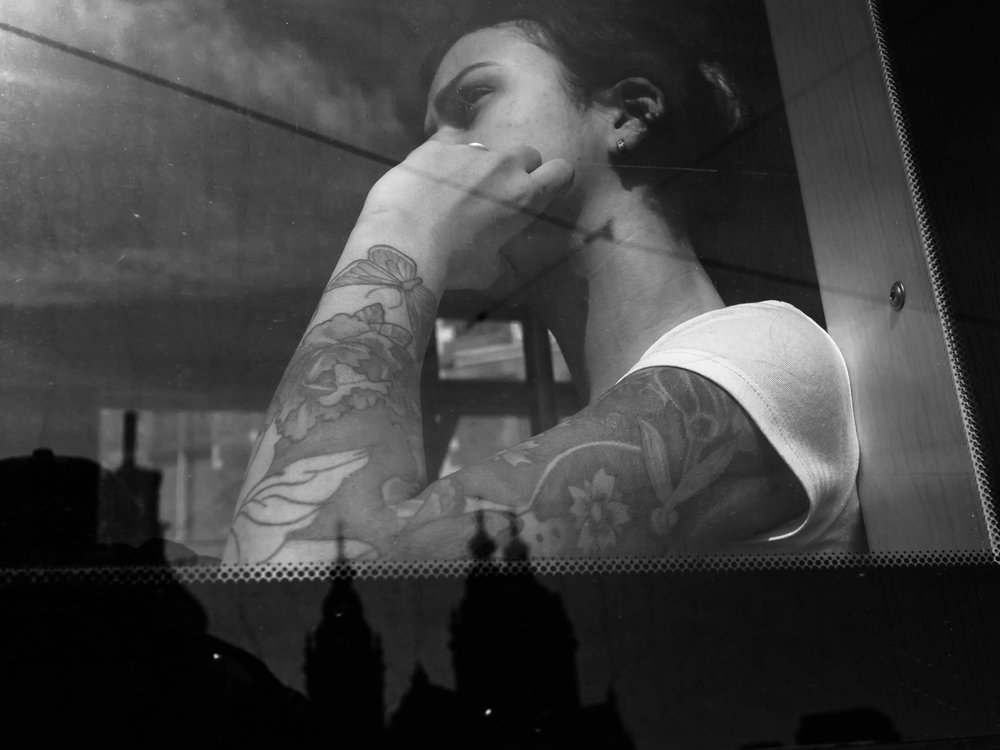 I saw this girl sitting in a tram at Amsterdam Central Station in April 2018. Her tattoo was very colorful with flowers and butterflies. During post processing I decided to transfer the photo into black and white. It creates a nice film noir atmosphere and the reflection of the church in the window adds to the photo in my opinion. I had to come very close with the 17mm. The lense was almost against the tram window. She must have seen me, but just ignored me. I thank her for that :-)   Olympus OM-D E-M1 Mark 2 with Olympus M.ZUIKO 17mm 1:1.8