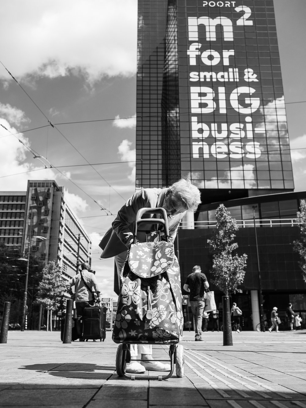 I made this photo in august 2018 near Rotterdam Central Station. This nice woman was busy getting something out of her trolley. In a split second I saw the text on the building behind her. Lucky me to create a funny combination between the text and her small trolley business.  Olympus OM-D E-M1 Mark 2 with Olympus M.ZUIKO 17mm 1:1.2 PRO