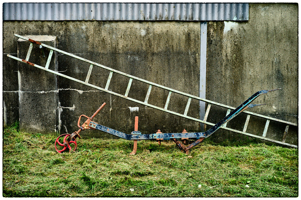 An old plough and ladders next to the barn at Yeo Farm, Devon.
