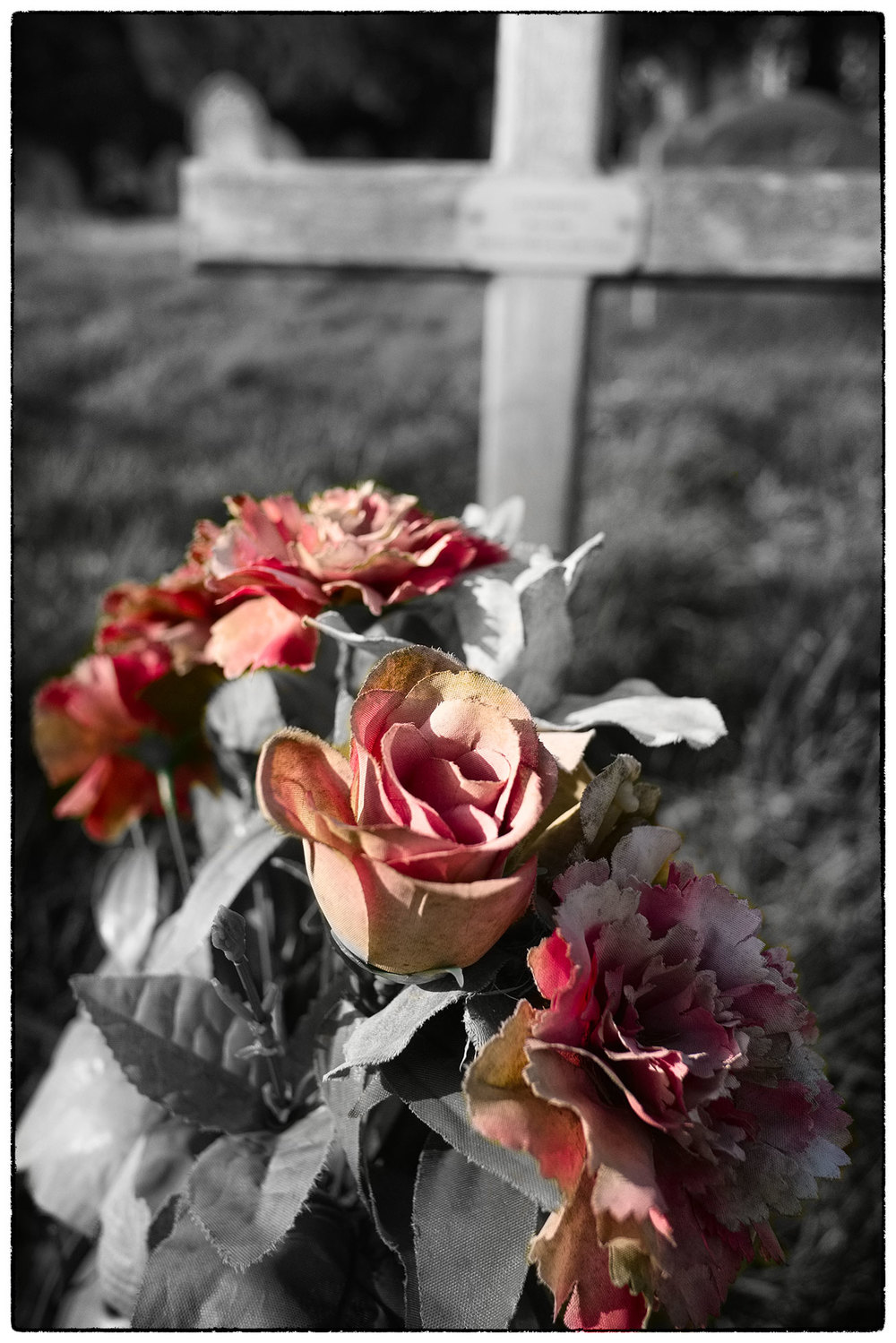 Artificial flowers in front of a simple cross.