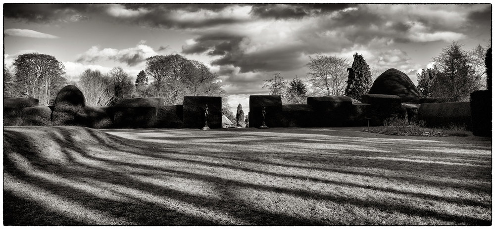 Topiary hedges, trees and long shadows, late afternoon in Chirk Castle gardens.