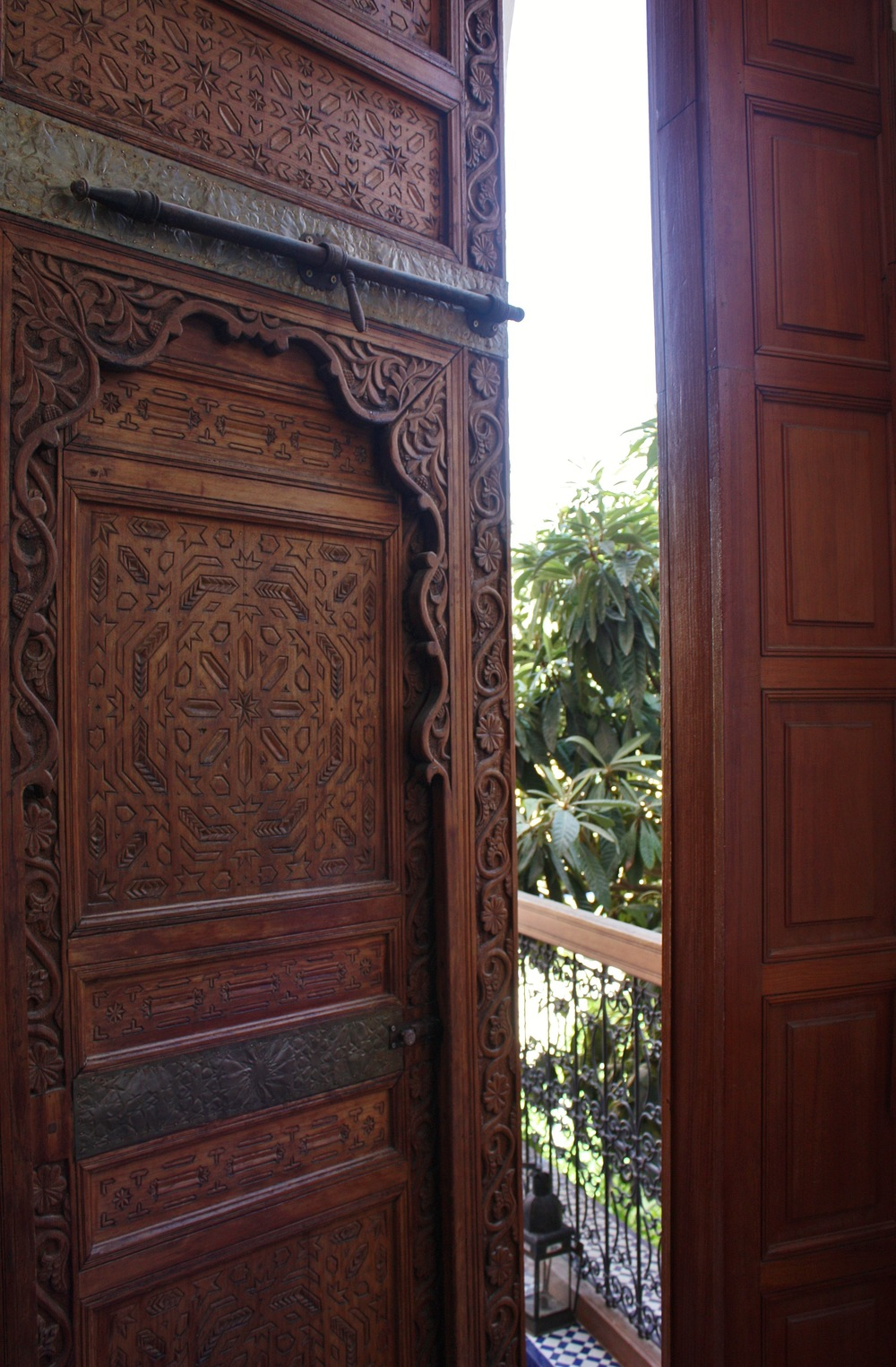 Massive wooden doors hand-carved with the Islamic star and geometric patterns characteristic of North Africa, from a riad in the old city of Fez, Morocco.