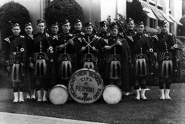 "Photo Courtesy of Jay Correia   Piedmont High School Kiltie Band ( circa 1933 - 1935). My grandfather, Milton Wallace, is on the far right. Photo taken 1933-1935, yearbooks would probably be able to exactly date the photo. He literally ""ran away"" to sea in December 1935, the middle of his senior year. He purchased his own pipes in 1938 in Melbourne, Australia, while in port there. I have that set.   Grandpa went on to play with the Golden Bear Pipe Band in Sacramento. I have his kilt, huge brass ""Golden Bear"" belt buckle, and sporran from that band. He played mostly to party, but inspired me to play. In 1952 Grandpa settled in Rio Vista, CA, my hometown. I believe that Golden Bear members would actually drive down river from Sacramento to practice at his house in Rio Vista. I'm sure lots of his homemade wine and other libations were had by all… [by Jay Correia]"