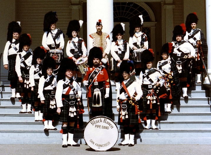 Photo courtesy of Carol Sawyer and Charlie Martin Left Rank: Ralph Voice Cameron McFadden Marjie Swiaja Charlie Martin PMaj Bill Cathro Right Rank: PSgt Fred Rutledge Roger Weed Carol Sawyer John Flynn Scott Tyree DMaj Jack Gerhardt Back: DSgt Dave Pollack Darleen Flynn Dick Lechnar Susan Wyatt Cheryl Gerhardt   Black Raven Pipe Band (1982) The Black Raven Pipe Band put on the Highland Games at the Dunsmuir House in the Oakland Hills. This is front the front steps of the Dunsmuir House. [by Carol Sawyer]