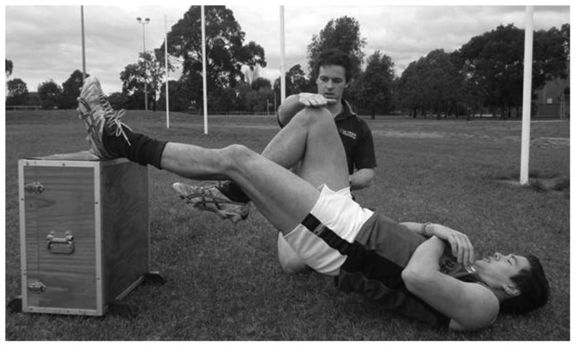 Grant Freckleton assessing hamstring muscle strength using the single leg hamstring bridge.