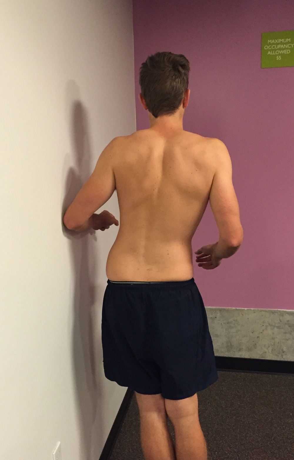 By placing the elbow against the wall it supports the trunk and allows the side gliding movement to be localised to the lumbar spine. Ask the patient to move their hips towards the wall stopping at the first point or discomfort or pain. Often on Day 1 this is only completed on one side.