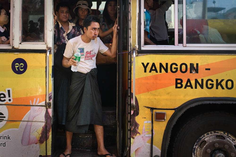 Man wearing tradition burmese skirt in yangon riding the bus.