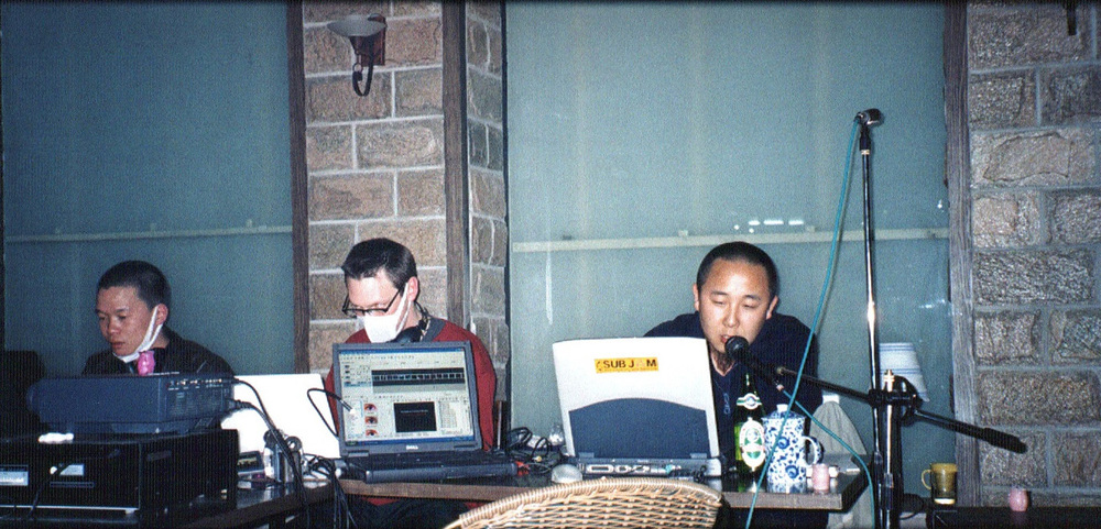 Christiaan Virant (center) and Zhang Jian (left) of FM3 perform with Yan Jun (right) and video artist Wu Quan at Wansheng Bookstore in Haidian, 8 April 2003.jpg