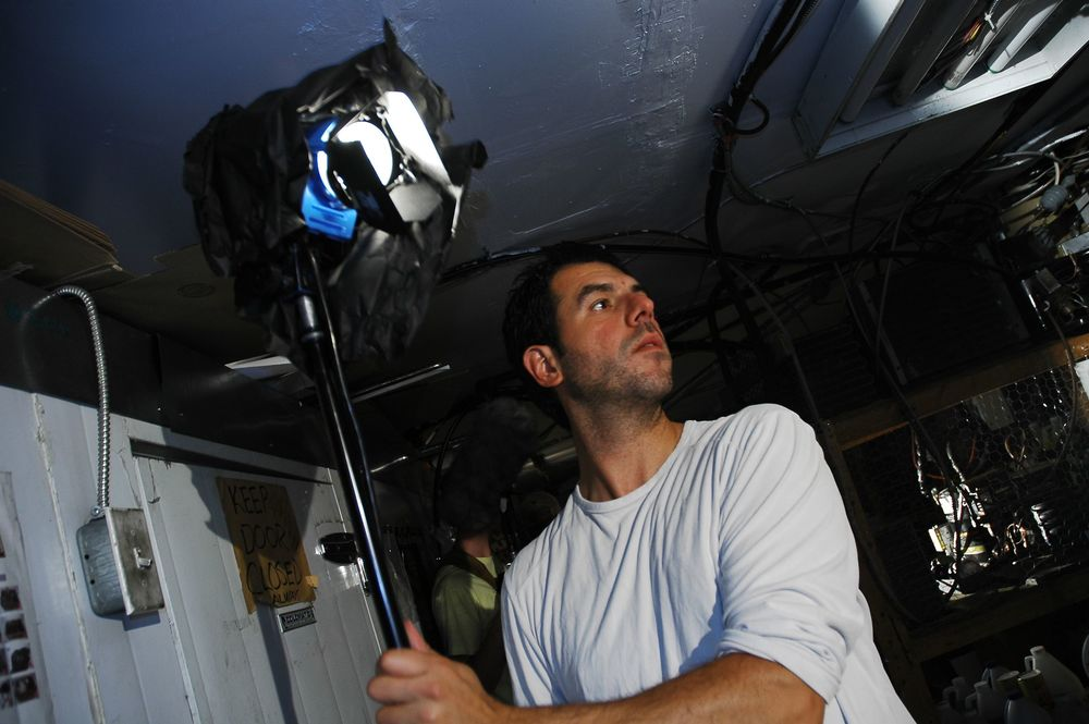 Cinematographer Alex Dacev setting a light
