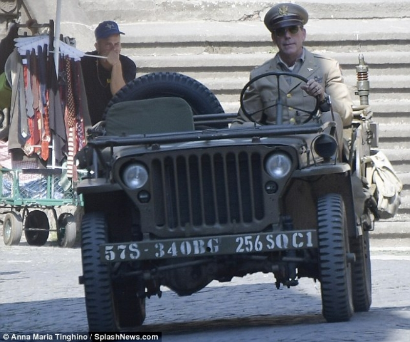 Impressive: Hugh looked convincing as his character when he wore his Major uniform in the front seat of the army car