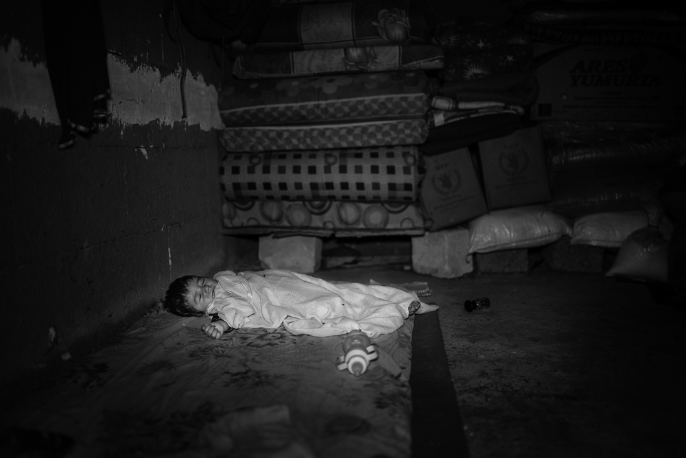 Child sleeping  in a Zakho under construction building