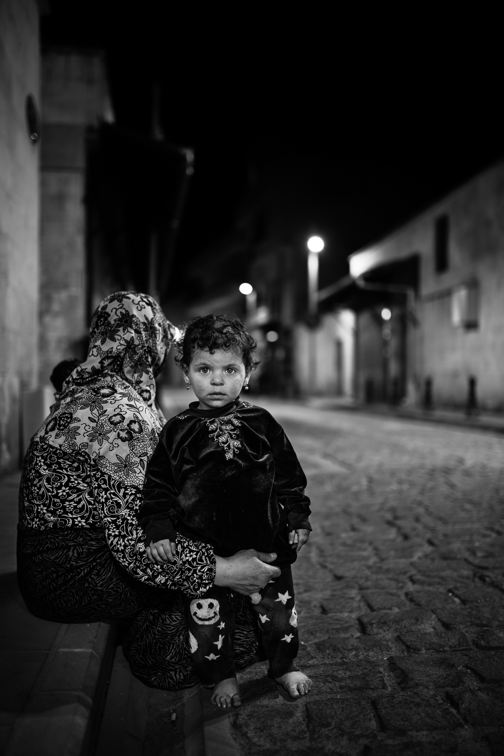 A little girl and his mother ask for charity on the roads of Gaziantep during the night