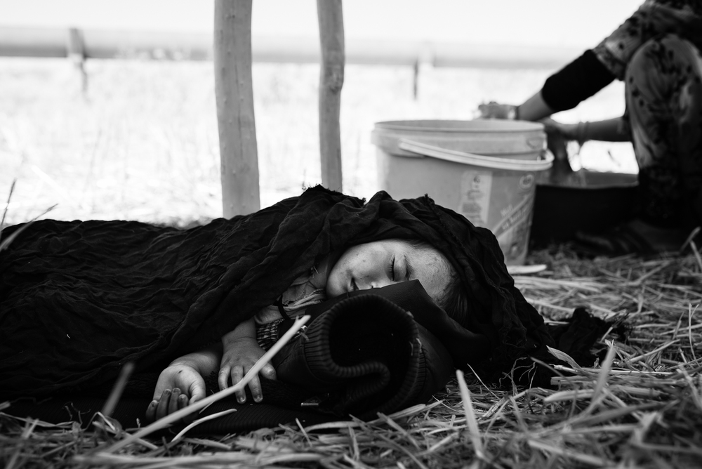 A little girl is sleeping while his mother washing some clothes in a refugees camp outside the Tal Abyad border. The video of this photo is  here
