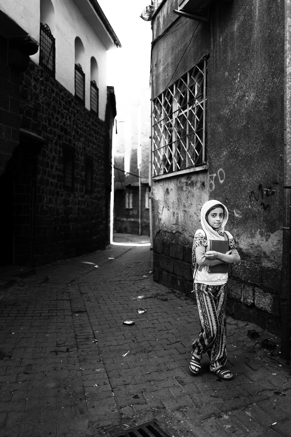 A girl is walking with the Quran in their hands, Diyarbakir (Turkey)