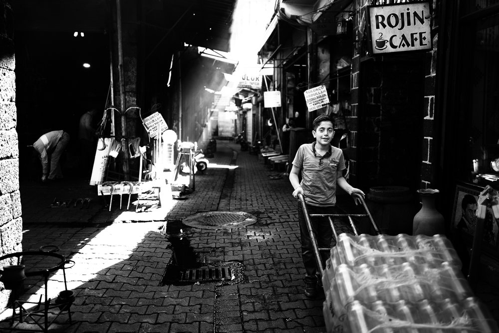 A little boy is carrying water bottles in a Diyarbakir's alley