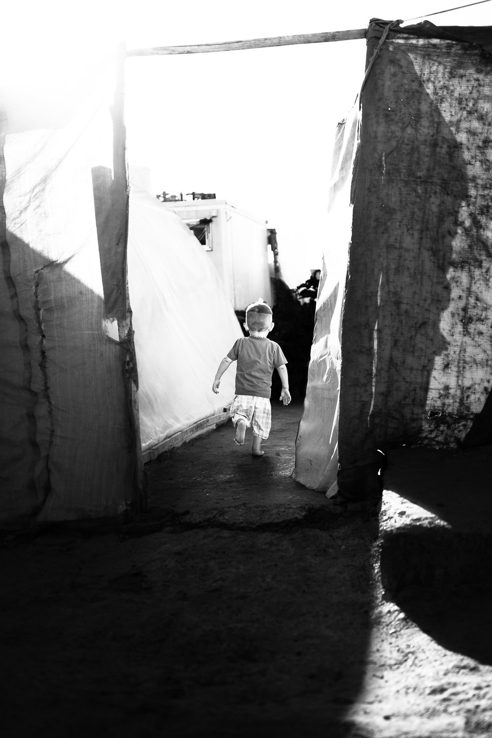 A little boy is running to his tent inside the Essian refugees, Iraq.