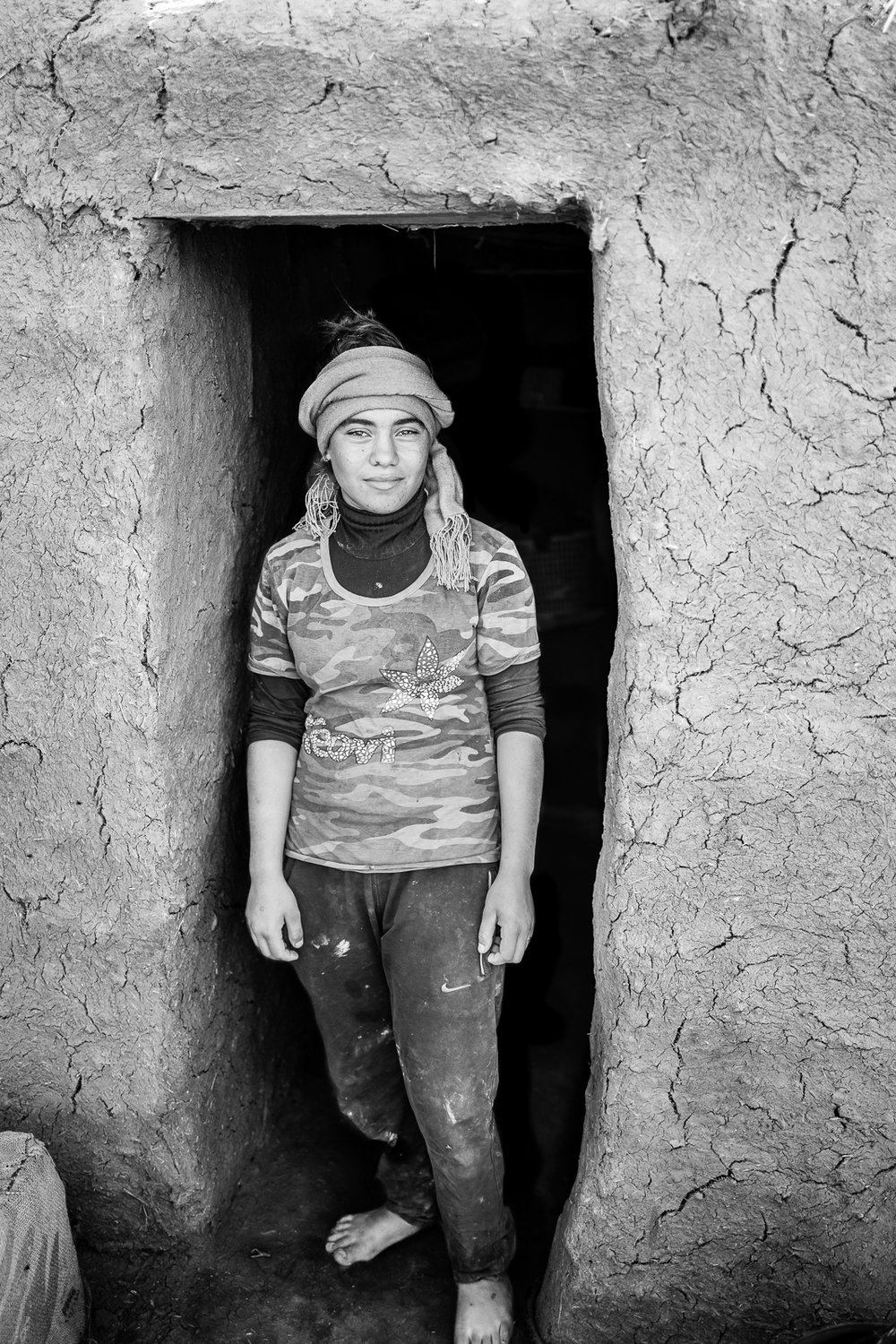 A girl is standing outside the door of her temporary home in a refugees camp in the desert, somewhere between Zakho and Sinjar. Iraq