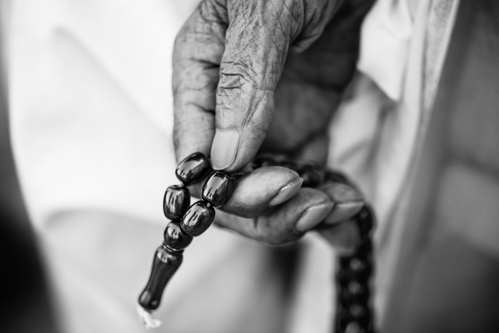 The hand of a elder woman, with her rosary, inside the Essian refugees, Iraq.