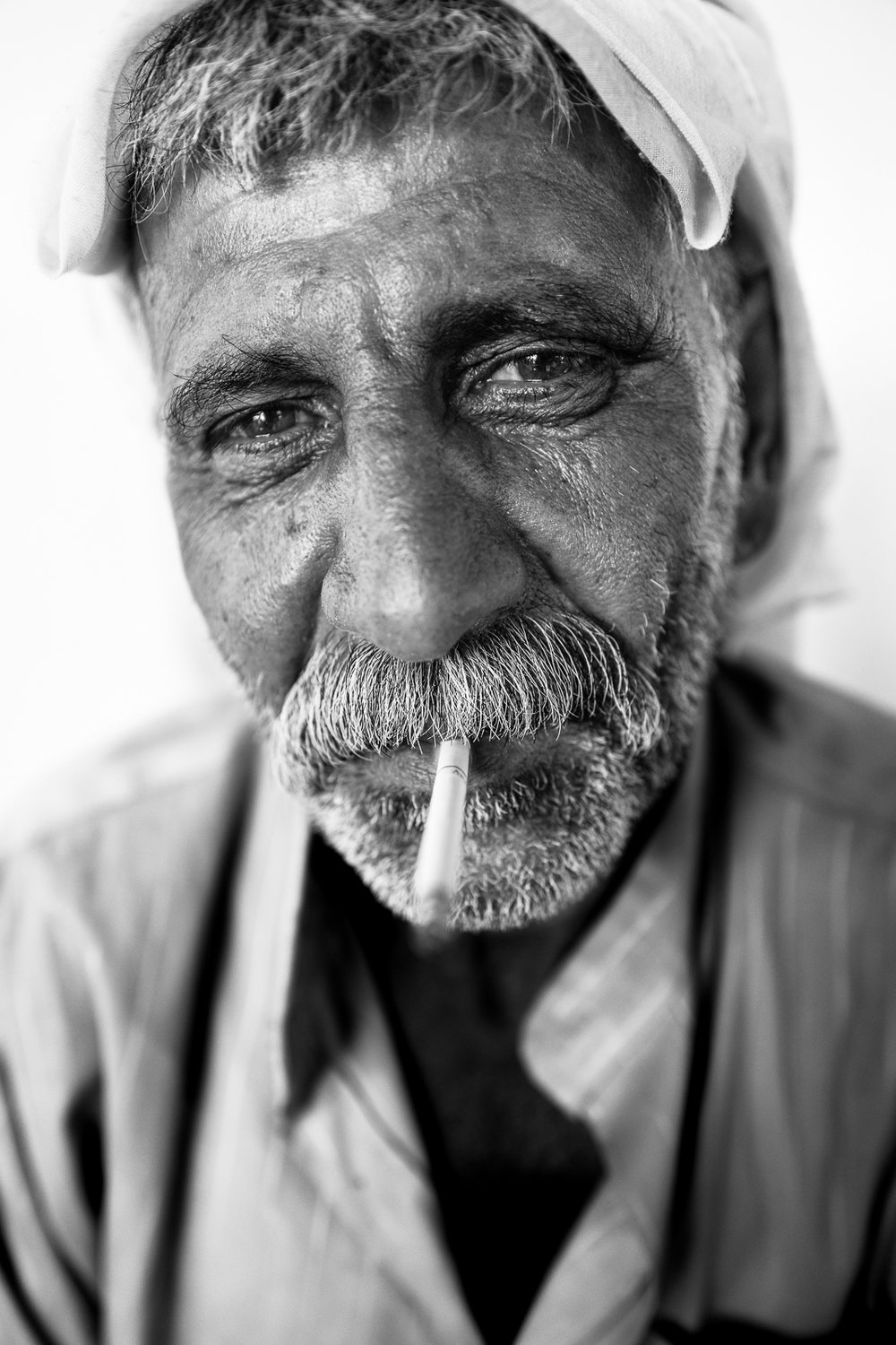 A Yazidi man and his cigarette inside Essian refugees camp, Iraq.