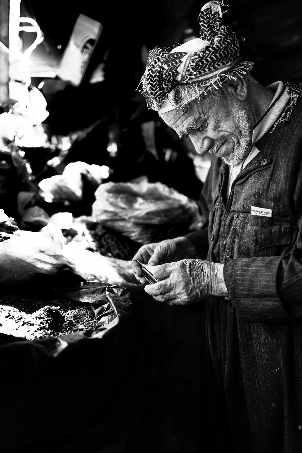 A man is making a cigarette in the Erbil bazaar