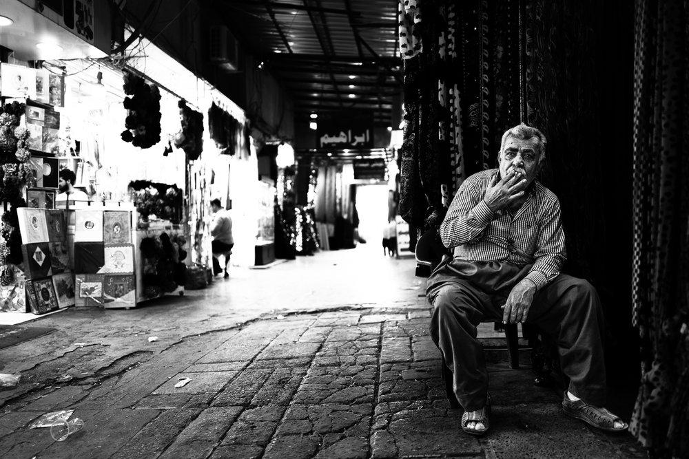 A carpet seller is taking a rest. Erbil bazaar