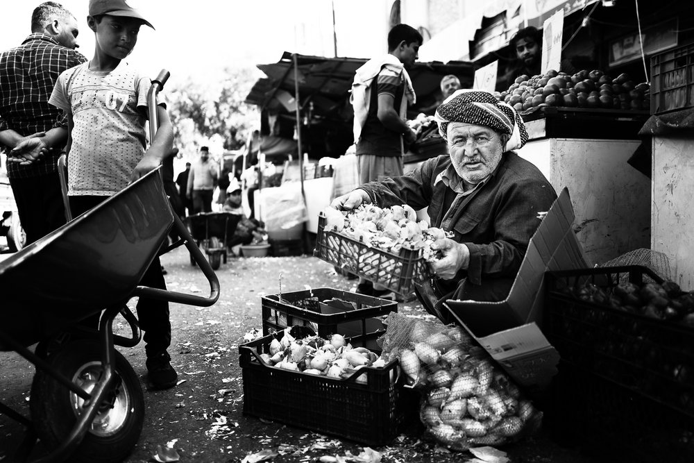 A seller of onions and potatoes in the Erbil bazaar
