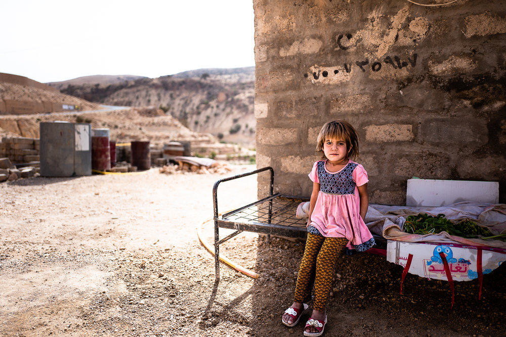 A little girl sits on her bed. Sinjar mount