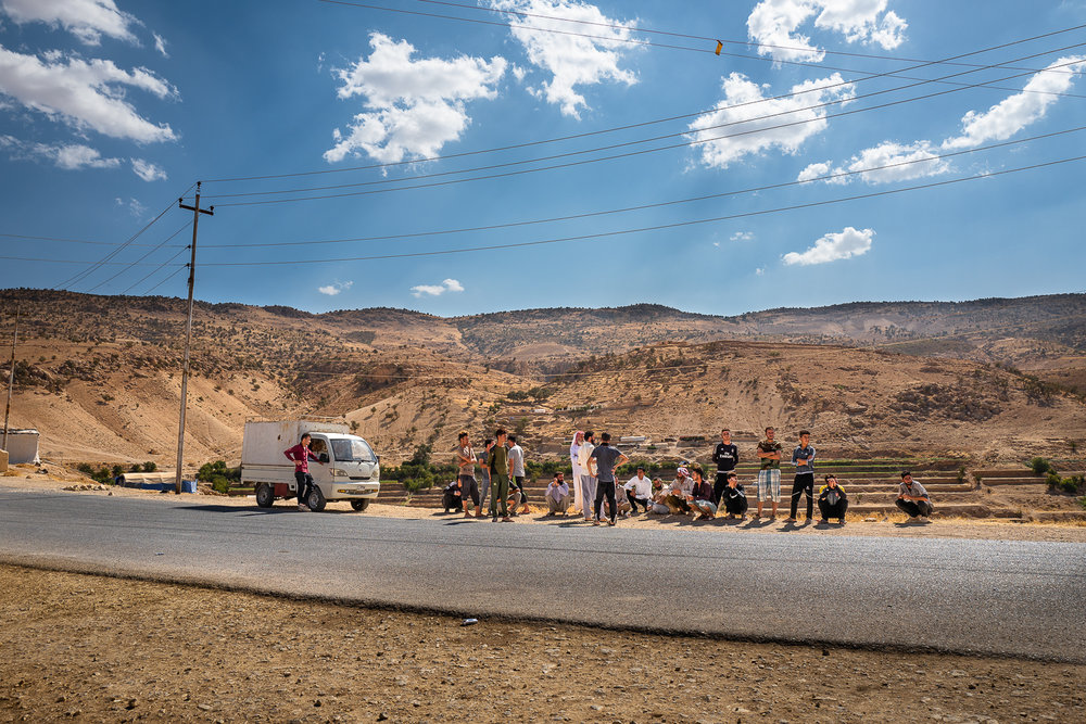 A group of people sit up in front of the tend where a sixteen years young girl has just killed herself due to the bad conditions of his life in the Sinjar mount
